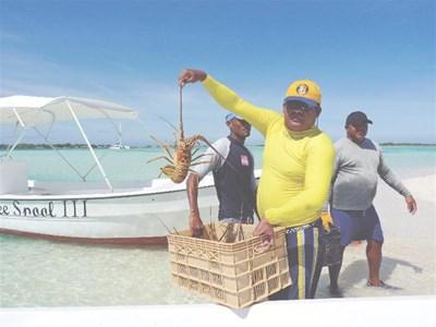 Рибари на един от островите в Лос Рокес гордо показват огромен омар.  СНИМКИ: АВТОРКАТА