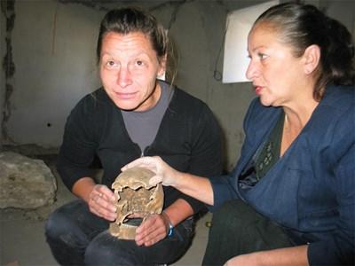 Реставраторът Екатерина Илиева и археологът Оленка Миланова показват извадения от гробницата череп на жена, която вероятно е живяла в прабългарската епоха. Снимка: Ваня Ставрева