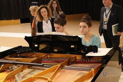 Децата седната зад роялите на виртуозите