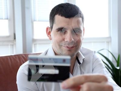 Георги Кънев държи банкова карта със залепен на нея стикер SkimProt СНИМКА: 24 часа