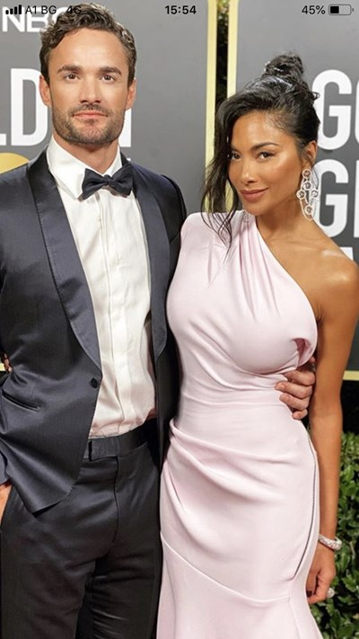 """Никол Шерцингер и Том Еванс вървят прегърнати на червения килим на 77-ото издание на наградите """"Златен глобус""""."""