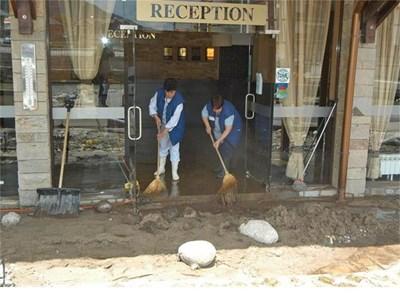Жени чистят наводнен и затлачен с тиня хотел в Банско. СНИМКА: БУЛФОТО