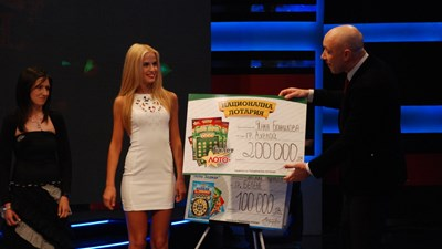 Захари Бахаров и асистентката му в Националната лотария връчват поредната голяма парична печалба. СНИМКА: Архив