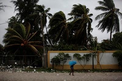 Жена се опитва да се предпази от мощния ураган в Хаити. Снимка: Ройтерс