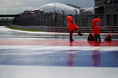 Руснаците се опитват да изчистят водата от пистата. СНИМКА: РОЙТЕРС