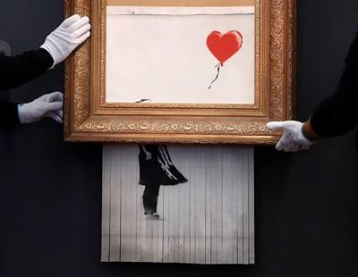 """""""Любовта е в кошчето"""" - произведението на британския графитист Банкси, което се самонаряза в реално време на търг, беше представено на изложба в германския град Баден-Баден СНИМКИ: РОЙТЕРС"""