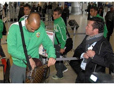 Лотар Матеус прибира бордната си карта на летището вчера при тръгването на отбора, а пред него вратарят Николай Михайлов тръгва към изхода. СНИМКА: ПИЕР ПЕТРОВ