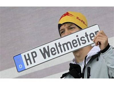 """Себастиан Фетел се радва на новия си номер от родния град Хепенхайм на който е изписан """"Световен шампион"""". С него той ще кара догодина личния си автомобил. СНИМКА: РОЙТЕРС"""