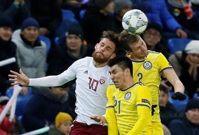 Латвиецът Велерийс Сабала (вляво) се сблъсква с казаха Абзал Бейсебеков при борба за висока топка в Астана, където мачът от Лигата на нациите завърши 1:1. СНИМКА: РОЙТЕРС