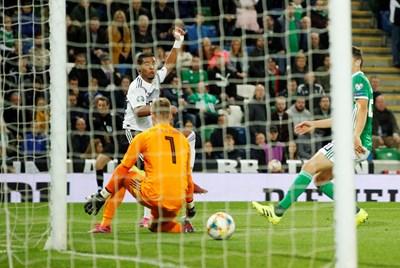 Серж Гнабри е мушнал топката покрай вратаря Пийкок-Фарел, за да оформи победата на Германия с 2:0 в Белфаст. СНИМКА: РОЙТЕРС