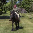 Кралица Елизабет язди кон в градините си.