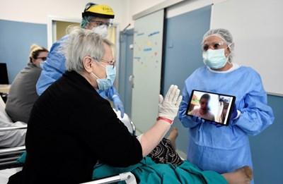 Пациент с коронавирус говори с таблет с роднина, който не може да го посети в болница в Милано. СНИМКА: РОЙТЕРС