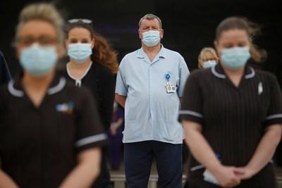Персоналът на болница почита с минута мълчание жертвите на вируса във Великобритания. В света са починали повече от 2,75 млн. души.   СНИМКА: РОЙТЕРС