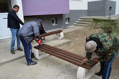 Работници сглобяват нови пейки в междублоково пространство