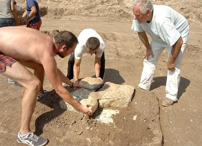 Археологът Костадин Кисьов и хора от екипа му повдигат каменните плочи от саркофага, в който е положена урната. СНИМКА: Наташа Манева