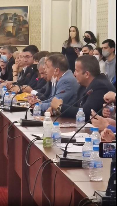 Иван Ангелов (със сивия костюм и смъкнатата маска) говори пред комисията Снимка: Фейсбук