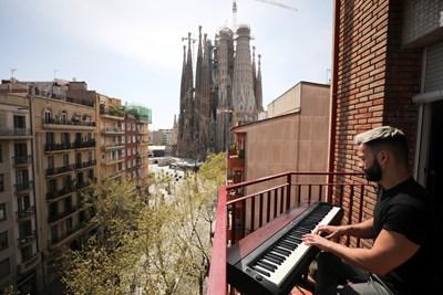 Пианистът Алберто свири на пиано на балкона си в Барселона, за да зарадва съседите си в пика на кризата Снимки: Ройтерс
