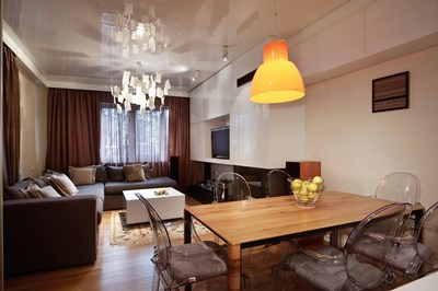 """Трапезарията с корпусната композиция срещу дивана, изработена по индивидуален проект. Камината е от """"Камини Ранков"""". От тавана се спуска култовата лампа с листенцата, дизайн на Инго Маурер"""
