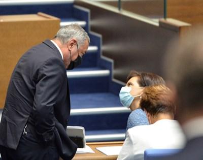 Лидерът на НФСБ Валери Симеонов и шефката на парламентарната група на ГЕРБ Даниела Дариткова разговарят в пленарната зала с маски на лицето.  СНИМКА: ЙОРДАН СИМЕОНОВ