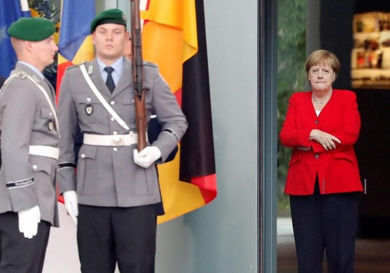 Ангела Меркел си държи ръцете скръстени на среща, за да не се вижда, че трепери.