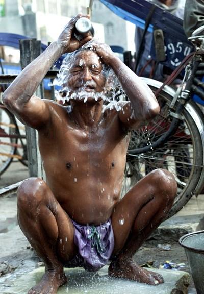 Когато човек иска да поддържа лична хигиена, той винаги намира начин - както прави този водач на рикша в Делхи, който се къпе на улицата СНИМКА: РОЙТЕРС