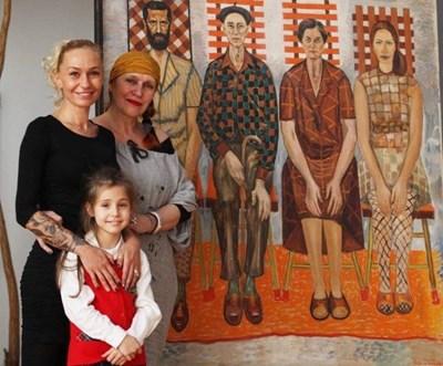 """Картината """"Семейство"""" на Златю Бояджиев. От ляво на дясно са синът му Георги, той самият, съпругата му Цена и дъщерята Радка. Пред картината са внучката му Цена, правнучката Елена и праправнучката Беатрис."""