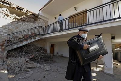 Мъж спасява телевизор от порутени сгради в Гърция. СНИМКА: РОЙТЕРС