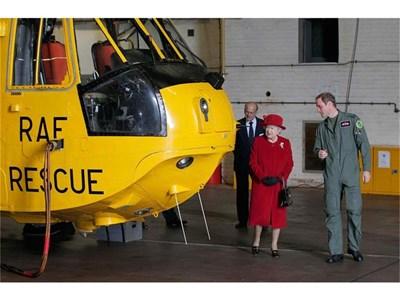 Принц Уилям показва на кралица Елизабет Втора и съпруга й принц Филип хеликоптера, с който лети от RAF Valley при спасителни операции.  СНИМКА: РОЙТЕРС