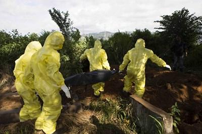 Мъже в защитни облекла погребват умрял от ебола в Гвинея. СНИМКА: РОЙТЕРС