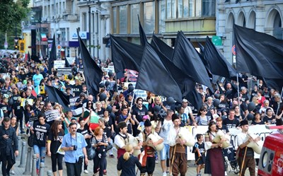 """Стотици близки на хора с увреждания излязоха на протест в понеделник вечер в столицата, облечени във фланелки """"Системата ни убива"""" и веещи черни знамена."""
