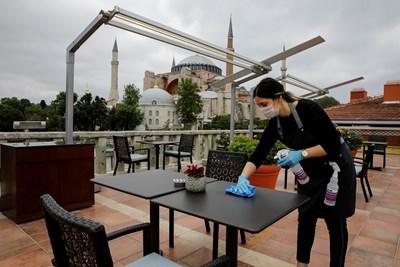 Служителка на хотел в Истанбул бърше масите в очакване на туристи.