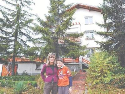 Диана Върбенова и синът й (вляво) пред къщата си в Горна баня, възстановена след удара на НАТО преди 10 години.