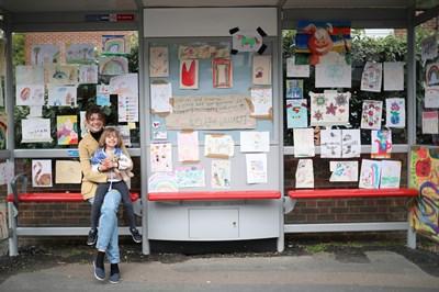 Майка и 4-годишната и? дъщеря Роузи седят на автобусна спирка в Лондон, където детето е подредило изложба с рисунки за коронавируса. СНИМКА: РОЙТЕРС