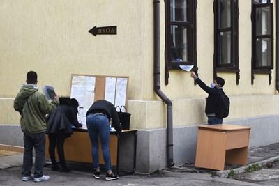 Служител на бюро по труда в София подава през прозореца документите на безработен,  дошъл да се  регистрира.