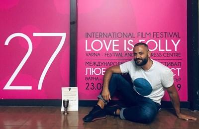 """Режисьорът Николай Василев, създал """"Формулата на Тео"""", позира пред плаката на фестивала заедно с наградата си. СНИМКА: Личен архив"""