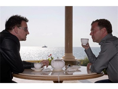 """Руският президент Дмитрий Медведев почерпи Боно с чай завчера в резиденцията """"Бочаров ручей"""" в Сочи, а после го разходи с електромобил до плажа. Двамата обсъдиха музикалните си пристрастия. Медведев призна, че обича хотдог, с какъвто го угостил преди време Барак Обама, но призна, че рядко си позволява такава храна. СНИМКИ: РОЙТЕРС"""