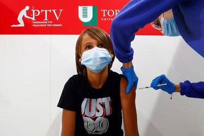 12-годишно момче получава ваксина в медицински център в Рим.