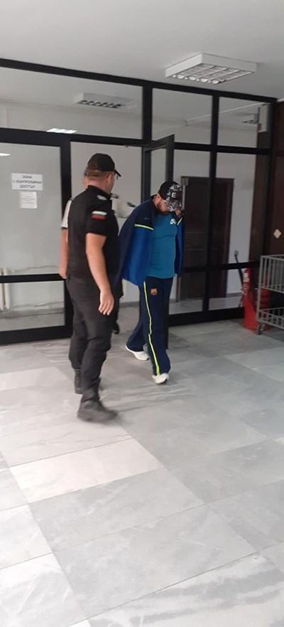 Съдебна охрана води Веселин в съдебната зала.