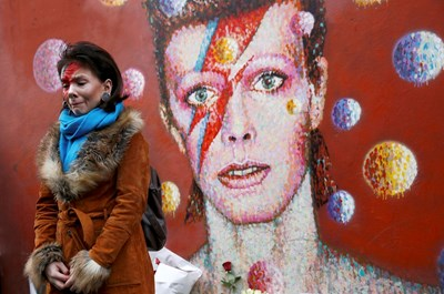 Почитателка на рок легендата Дейвид Бауи скърби пред графит с неговия лик в Лондон след съобщение, че той е починал. СНИМКА: РОЙТЕРС
