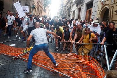 Италианци чупят бариери на протест в Рим срещу въвеждането на ваксинационни паспорти, с които ще пускат в ресторанти, на спортни и културни събития от следващата седмица. СНИМКА: РОЙТЕРС