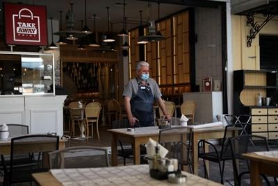 Собственик на ресторант в Атина чака клиенти, след като заведенията отвориха. СНИМКА: РОЙТЕРС