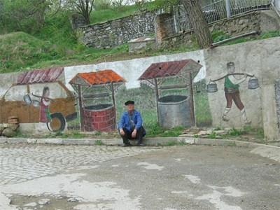Самоукият художник Йордан Калагларски пред негова творба на улица в селото. СНИМКА: Любомир Илков