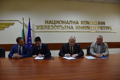 Шефът на НКЖИ Красимир Папукчийски (вторият от дясно на ляво) подписва договора с представители на фирмите в консорциума.