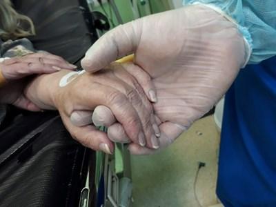 Радослава успява да снима как лекар държи ръката на пациентка.