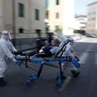 Медици карат пациент на носилка по улица в Неапол.