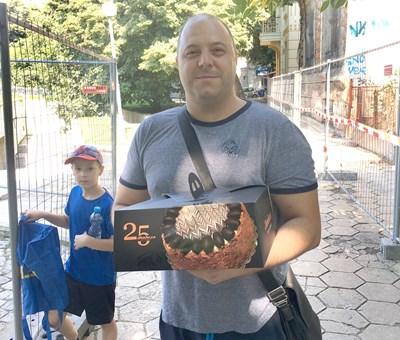 Тодор Тодоров върви с торта към общината, с него е синът му Димитър. Снимка: Авторът