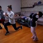 Китайско семейство прави гимнастика с бутилки вода, докато има забрана да напуска дома си заради епидемията.
