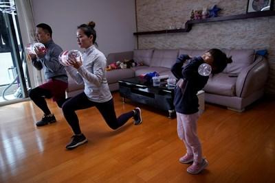 Китайско семейство прави гимнастика с бутилки вода, докато има забрана да напуска дома си заради епидемията. СНИМКА: РОЙТЕРС