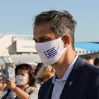 Гръцкият министър на туризма Хари Теохарис с маска ма лицето посреща германски туристи.
