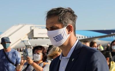 Гръцкият министър на туризма Хари Теохарис с маска ма лицето посреща германски туристи. СНИМКА: РОЙТЕРС